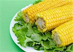 sweet corn cobs and lettuce leaves on white plate Stock Photo - Royalty-Free, Artist: AlexStar                      , Code: 400-04444285