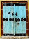 Old wooden door painted light blue with black metal decorations