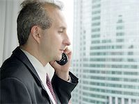 Businessman by the window talking on the phone Stock Photo - Royalty-Freenull, Code: 400-04463980