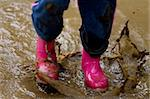 A little girls pink boots splashing in a muddy puddle