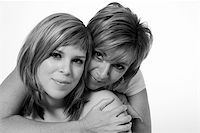 A portrait taken from mother and daughter taken on a white background holding on to each other Stock Photo - Royalty-Freenull, Code: 400-04481985