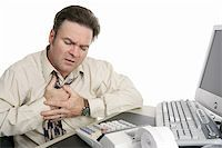 A middle aged man having chest pains or indigestion at work. Stock Photo - Royalty-Freenull, Code: 400-04486183