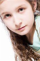 Studio portrait of a young girl looking concentrated Stock Photo - Royalty-Freenull, Code: 400-04486485