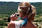 A blonde woman is taking a photo with her black digital camera Stock Photo - Royalty-Free, Artist: myper                         , Code: 400-04486489