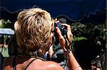 A blond woman is taking a photo with her black digital camera Stock Photo - Royalty-Free, Artist: myper                         , Code: 400-04486490