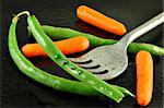 Fresh green beans and baby carrots pierced with a fork on a watery black plate Stock Photo - Royalty-Free, Artist: karimala                      , Code: 400-04499251