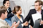 Business people shaking hands making an agreement in the plane