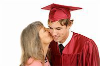 Young graduate receiving a kiss from his mother.  Isolated on white. Stock Photo - Royalty-Freenull, Code: 400-04513936
