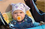 Pretty little girl with baby's dummy sit in carriage. In kerchief and jeans catsuit. Stock Photo - Royalty-Free, Artist: alexpurs                      , Code: 400-04524378