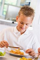 Schoolboy enjoying his lunch in a school cafeteria Stock Photo - Royalty-Freenull, Code: 400-04536440