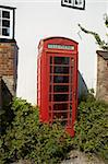 An old red telephone box by a white wall Stock Photo - Royalty-Free, Artist: markabond                     , Code: 400-04560200