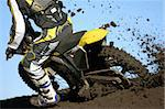 A rear view of a motocross rider races through the dirt and mud during a race. Stock Photo - Royalty-Free, Artist: sportlibrary                  , Code: 400-04562628