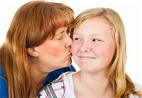 Mother kissing her pretty blond daughter who looks embarassed.  White background. Stock Photo - Royalty-Freenull, Code: 400-04585459