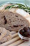 Half a loaf of olive and rosemary bread with a sprig of rosemary on top of a wood cutting board.  A ramekin of olives on the side. Stock Photo - Royalty-Free, Artist: janmin                        , Code: 400-04601201
