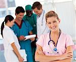 Smiling nurse with doctors in the background Stock Photo - Royalty-Free, Artist: 4774344sean                   , Code: 400-04608067