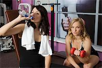 two girls in fitness club one drinking water and the other doing exercise Stock Photo - Royalty-Freenull, Code: 400-04609949