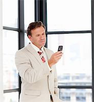 Portrait of a mature businessman sending a text on a mobile phone Stock Photo - Royalty-Freenull, Code: 400-04614551