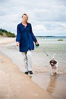 Woman walking the dog on the beach Stock Photo - Royalty-Freenull, Code: 400-04618367