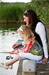Young girl by the waterside with her mom trying to catch a fish Stock Photo - Royalty-Free, Artist: Fotosmurf                     , Code: 400-04619572
