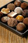 A small assortment of chocolate truffles and pralines on a serving dish.  Very Shallow depth of field, focusing across the middle.  Stock Photo - Royalty-Free, Artist: sumners                       , Code: 400-04629839