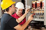 Apprentice electrician works on an industrial power distribution center while his supervisor looks on. Stock Photo - Royalty-Free, Artist: lisafx                        , Code: 400-04631524