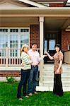 Happy couple getting keys to new house from real estate agent Stock Photo - Royalty-Free, Artist: Elenathewise                  , Code: 400-04633773