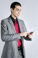 Businessman with gray suit talking cellular phone with suit and red tie Stock Photo - Royalty-Freenull, Code: 400-04649192