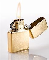 Flaming golden lighter on a white background Stock Photo - Royalty-Freenull, Code: 400-04654267
