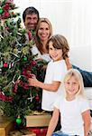 Portrait of a happy family decorating a Christmas tree at home Stock Photo - Royalty-Free, Artist: 4774344sean                   , Code: 400-04660016