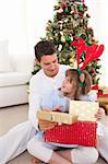 Smiling father and his daughter opening Christmas gifts at home Stock Photo - Royalty-Free, Artist: 4774344sean                   , Code: 400-04660034