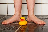 Feet of boy in shower with a lonely rubber duck Stock Photo - Royalty-Freenull, Code: 400-04661405