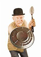 Senior in bowler hat defending himself with spoon and can lid Stock Photo - Royalty-Freenull, Code: 400-04670524