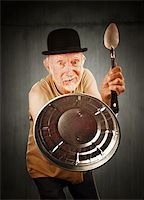 Senior in bowler hat defending himself with spoon and can lid Stock Photo - Royalty-Freenull, Code: 400-04670525