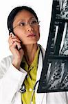 Asian female doctor looking at an MRI scan while talking on a cellphone. Vertical shot. Isolated on white. Stock Photo - Royalty-Free, Artist: edbockstock                   , Code: 400-04674096