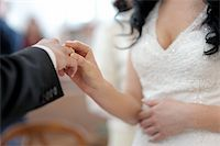 Bride is putting the ring on groom's finger Stock Photo - Royalty-Freenull, Code: 400-04683836