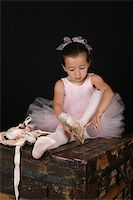 Cute little brunette girl trying on ballet pointe shoes Stock Photo - Royalty-Freenull, Code: 400-04712806