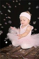 Cute blond toddler in ballet tutu reaching out to touch bubbles Stock Photo - Royalty-Freenull, Code: 400-04718879