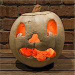 Lit white jack o'lantern on a table in front of a brick wall at night square Stock Photo - Royalty-Free, Artist: sgoodwin4813                  , Code: 400-04722936