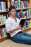 Good-looking young man holding a book stting on the floor in a bookstore Stock Photo - Royalty-Free, Artist: 4774344sean                   , Code: 400-04724143