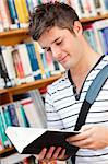 Cute male student reading a book in a bookstore Stock Photo - Royalty-Free, Artist: 4774344sean                   , Code: 400-04724145