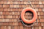 An orange lifesaver hanging on a wooden boathouse