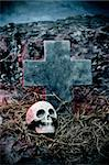 closeup of a stone cross and a skull in a cemetery for Halloween
