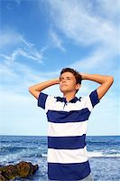 boy teenager hands in head relaxed in blue ocean sea beach summer vacation Stock Photo - Royalty-Freenull, Code: 400-04736368