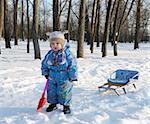 Winter games children - girl with a sledge in the park Stock Photo - Royalty-Free, Artist: vblinov                       , Code: 400-04753145