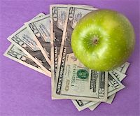 education loan - A green apple sits on top of a pile of $20 bills to illustrate the cost of education, food, or health care. Stock Photo - Royalty-Freenull, Code: 400-04758612