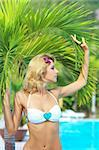 Beautiful woman near swimming pool under palm tree Stock Photo - Royalty-Free, Artist: GoodOlga                      , Code: 400-04784268