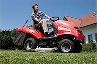 Man riding lawn mower in backyard Stock Photo - Premium Royalty-Freenull, Code: 649-04827412