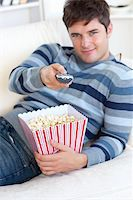 Relaxed young man eating popcorn and holding a remote lying on the sofa at home Stock Photo - Royalty-Freenull, Code: 400-04841242