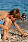 little boy playing with rocks on pebble beach by blue sea Stock Photo - Royalty-Free, Artist: simply                        , Code: 400-04843269