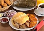 Typical Peruvian breakfast consisting of Pan con Chicharron (Bun with fried meat) and fried sweet potato, tamal (in the back), salsa criolla (onion salad) with coffee, orange juice and buns (Selective Focus, Focus on the front) Stock Photo - Royalty-Free, Artist: ildi                          , Code: 400-04857072